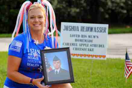 Lisa Heintz holding her son's portrait at the Freedom 4 miler