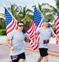 four men holding the american flag while running